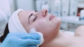 The cosmetologist cleans off beautiful woman's face from the beauty mask. Cosmetic procedure, skincare. Taking care of. The cosmetologist cleans off stock video