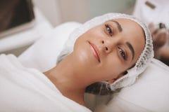 Cosmetologist de visita da jovem mulher bonita na clínica da beleza imagens de stock