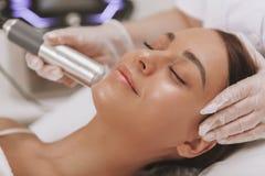 Cosmetologist de visita da jovem mulher bonita na clínica da beleza imagens de stock royalty free