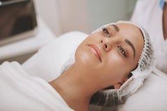 Cosmetologist de visita da jovem mulher bonita na clínica da beleza imagem de stock royalty free