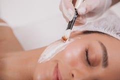 Cosmetologist de visite de belle jeune femme à la clinique de beauté images stock
