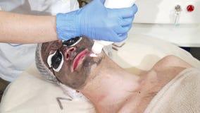 Cosmetologist, der den Gesichtskohlenstoff abzieht für männlichen Kunden tut stock video
