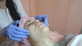 Cosmetologist, der geduldige Haut in der Schönheitsklinik anwendet eine Sahnemaske reinigt stock video