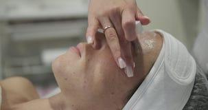 Cosmetologist, der Gesichtscreme am Badekurort aufträgt stock video footage