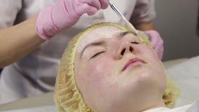 Cosmetologist, der Gesichtsmaske an der Problemhaut anwendet junge Frau, die das Hautverfahrenssäubern hat stock video footage