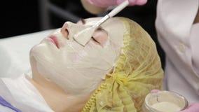 Cosmetologist, der Gesichtsmaske an der Problemhaut anwendet junge Frau, die das Hautverfahrenss?ubern hat stock video footage