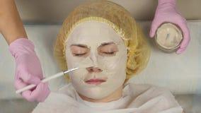 Cosmetologist, der Gesichtsmaske an der Problemhaut anwendet junge Frau, die das Hautverfahrenss?ubern hat 4K stock footage