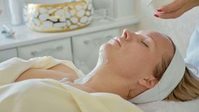 Cosmetologist die het roommasker op het gezicht van jonge mooie vrouw toepassen Stock Foto's