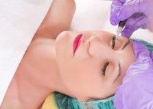 Cosmetologist die permanent eyeliner maken omhoog maken royalty-vrije stock afbeeldingen
