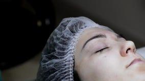 Cosmetologist die permanente make-up op wenkbrauw-wenkbrauw tatoegering toepassen stock videobeelden