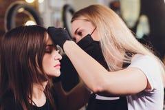 Cosmetologist die wenkbrauwenontwerp maken Aantrekkelijke vrouw die gezichtszorg krijgen bij schoonheidssalon Perfecte Architectu royalty-vrije stock foto's
