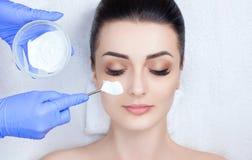 Cosmetologist dla procedury czyścić skórę i nawilżać, stosuje maskę z kijem twarz kobieta w b Obraz Royalty Free