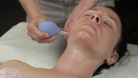 Beautician does anti-aging neck massage with vacuum banks. vacuum face massage for skin regeneration stock video