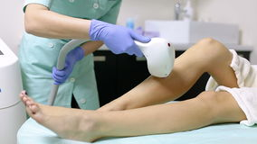 Cosmetologist does laser hair removal on legs of patient. Epilation procedure. Cosmetologist does laser hair removal on the legs of the patient. Epilation stock footage