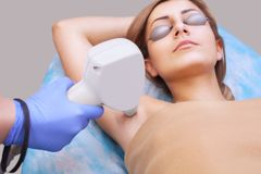 The cosmetologist does the laser hair removal procedure in the armpit zone, Royalty Free Stock Photo