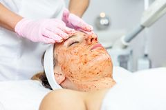 Cosmetologist is doing Face peeling mask, spa beauty treatment for young girl. Model, close-up. Cosmetological clinic. Healthcare. Cosmetologist is doing Face Stock Photos