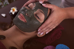 Cosmetologist doing massage on the woman`s face in spa salon. Royalty Free Stock Images