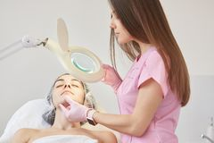 Cosmetologist dresses pink madical gown, latex gloves examines patient face, finds defects under lamp, prepering woman for royalty free stock photo
