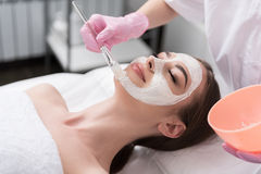 Cosmetologist is employing anti-aging agent for face. Enjoying procedure. Attractive young woman is getting facial mask at spa. She is lying and relaxing. Her Royalty Free Stock Photos