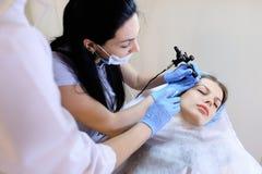 Cosmetologist féminin faisant la procédure tatouante pour la femme par la machine Images libres de droits