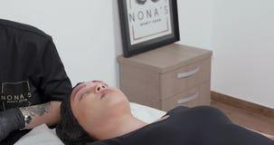 Cosmetologist fêmea novo que limpa as sobrancelhas após ter microblading o procedimento filme