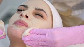 Cosmetologist in gloves wiping skin care mask from woman face, closeup portrait.
