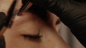 Cosmetologist hand pulls out eyebrows. Close-up of a cosmetologist`s hand pulls out the beautiful patient`s eyebrow with a pair of tweezers. Part of the eyebrow stock footage