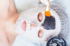 Cosmetologist i brunnsortsalongen som applicerar gyttjaframsidamaskeringen genom att använda borsten Arkivbilder