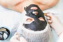 Cosmetologist i brunnsortsalongen som applicerar gyttjaframsidamaskeringen genom att använda borsten Royaltyfria Foton