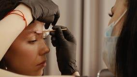 Cosmetologist k?mmt die Augenbrauen stock footage