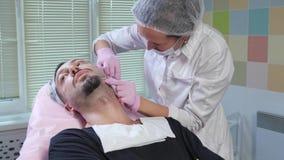 Cosmetologist legt eine Einspritzung einem Mann vor stock video footage