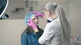 Cosmetologist maakt brow tatoeërend in salon langzame motie stock video