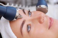 Cosmetologist maakt de procedure het ultrasone schoonmaken van de gezichtshuid stock foto's