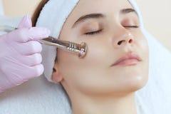 Cosmetologist maakt de procedure Microdermabrasion van de gezichtshuid van een mooie, jonge vrouw in een schoonheidssalon royalty-vrije stock foto's