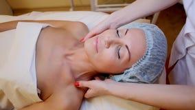 Cosmetologist maakt een vrouwengezicht en neck massage Spa stock videobeelden