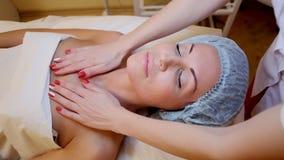 Cosmetologist maakt een vrouwengezicht en neck massage Spa stock footage