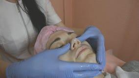 Cosmetologist maakt massage van neus stock video