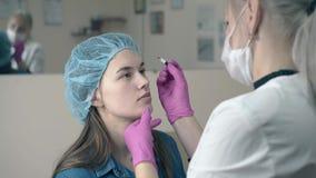 Cosmetologist maakt tekens op meisjesgezicht voor permanente make-up stock videobeelden