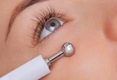 Cosmetologist maakt tot de apparaten een procedure van Microcurrent-therapie van een mooie, jonge vrouw in een schoonheidssalon Stock Foto's