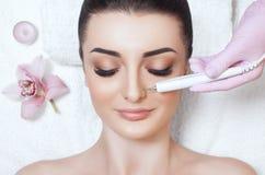 Cosmetologist maakt tot de apparaten een procedure van Microcurrent-therapie van een mooie, jonge vrouw in een schoonheidssalon stock fotografie
