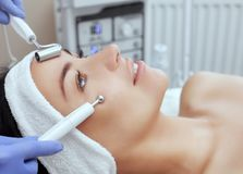 The cosmetologist makes the apparatus a procedure of Microcurrent therapy of a beautiful, young woman in a beauty salon stock photos