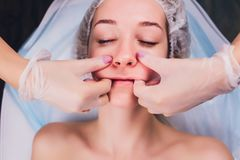 Cosmetologist makes a buccal massage of the patient`s facial muscles. Cosmetologist makes a buccal massage of the patient`s facial muscles royalty free stock images