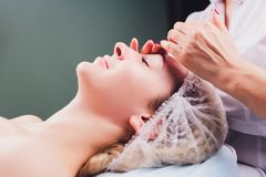 Cosmetologist makes a buccal massage of the patient`s facial muscles. royalty free stock image
