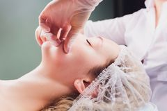 Cosmetologist makes a buccal massage of the patient`s facial muscles. Cosmetologist makes a buccal massage of the patient`s facial muscles royalty free stock image