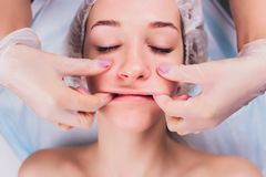 Cosmetologist makes a buccal massage of the patient`s facial muscles. Cosmetologist makes a buccal massage of the patient`s facial muscles stock photography