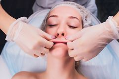 Cosmetologist makes a buccal massage of the patient`s facial muscles. Cosmetologist makes a buccal massage of the patient`s facial muscles royalty free stock photography