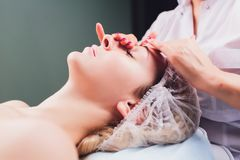 Cosmetologist makes a buccal massage of the patient`s facial muscles. Cosmetologist makes a buccal massage of the patient`s facial muscles royalty free stock photos