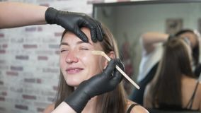 Cosmetologist makes eyebrow correction for young woman. Eyebrow master make a form with wax. Master applies wax over eyebrow and tears it off with hair stock video footage