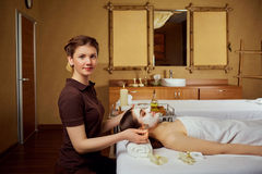 Cosmetologist makes a face mask for a woman in  spa salon Stock Photo