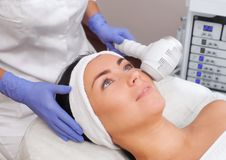 The cosmetologist makes the procedure Cryotherapy of the facial skin. Of a beautiful, young woman in a beauty salon.Cosmetology and professional skin care Stock Photography